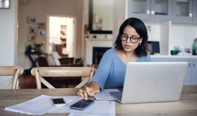 Shot of a young woman using a laptop and calculator while working from home